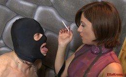 De slaaf knielt voor Ella Kross als asbak