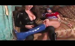 Vrouw in latex neukt haar vriendin met een voorbind dildo