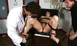 Vrouw vastgebonden op de tafel bij de dokter