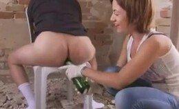Ella Kross stopt een bierflesje in zijn kont